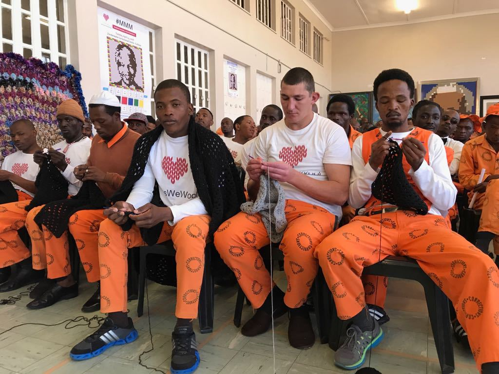 Inmate participants of the Massive Mandela Masterpiece knit their blankets during the event